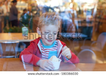 cute cheerful little boy eating ice-cream in cafe, view from outside through the window - stock photo