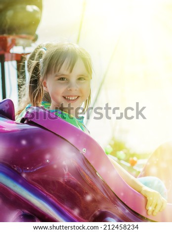 Cute cheerful little girl is riding on the carousel.