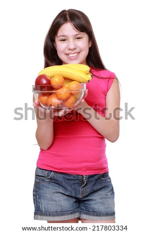 Cute cheerful little girl smiles while holding fruits isolated over white