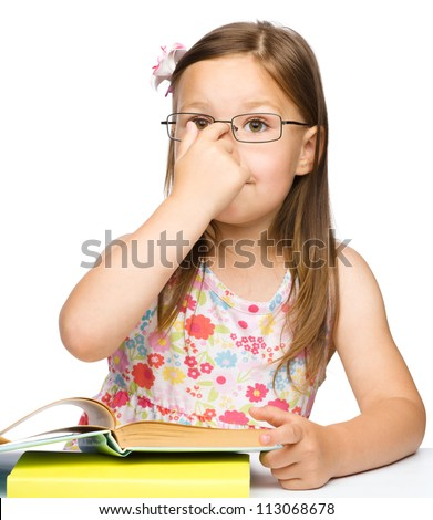 Cute cheerful little girl with book adjusting glasses on her nose, isolated over white - stock photo