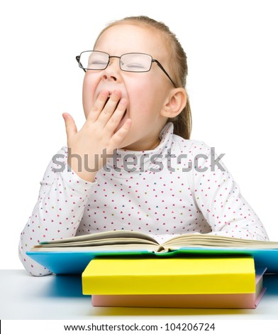 Cute cheerful little girl yawning while reading book and wearing glasses, isolated over white - stock photo