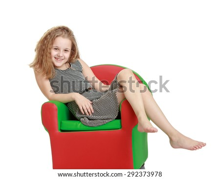 Cute cheerful teenage girl lay colored leather chair - isolated on white background - stock photo