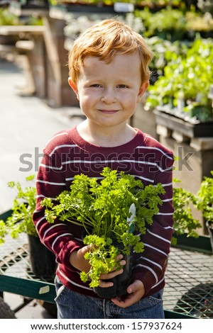 cute child at plant nursery smiling at the camera  with Spinach. please  view my portfolio for more images from this series.  - stock photo