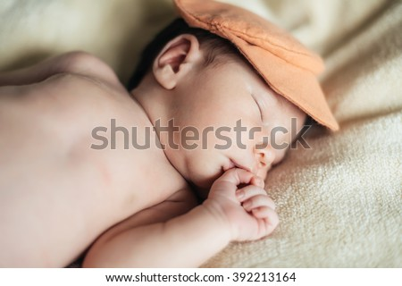 Cute child baby boy with yellow tulips in a waistcoat and a cap. Mothers day, spring concept. - stock photo