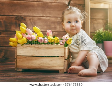 Cute child baby girl with a bouquet of tulips. Mothers day, spring concept. - stock photo