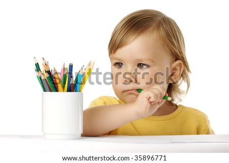 Cute child bites green crayon and thinks about new drawing ideas, isolated over white - stock photo