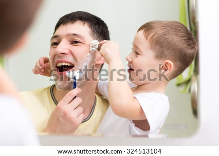 cute child boy and his father shave looking at mirror in bathroom - stock photo