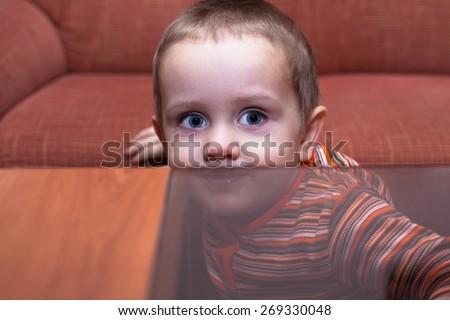 Cute child boy hiding behind table - stock photo