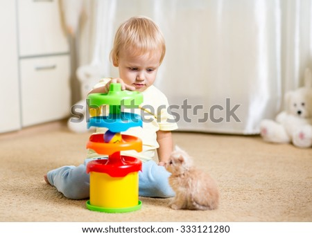 Cute child boy plays with a kitten, an interior - stock photo