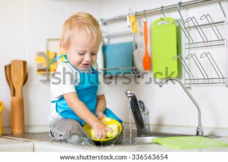 Cute child boy 2 years old washing up in kitchen - stock photo