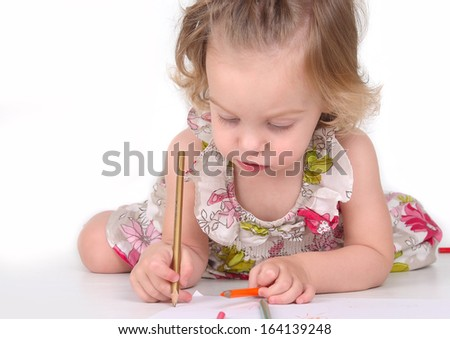 Cute child draws with colored pencils isolated on white - stock photo