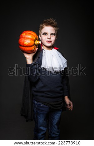 Cute child dressed as a vampire for Halloween party and holding a orange pumpkin. Studio portrait over black background - stock photo