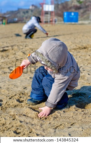 Cute child dressed in warm hooded clothes playing on the beach reaching down to touch the sand with one hand while holding a little orange plastic trowel in the other, - stock photo