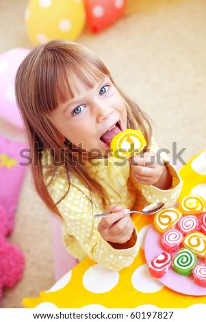 Cute child eating candies at home - stock photo