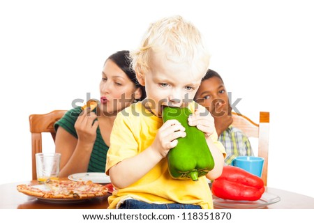 Cute child eating healthy green pepper and woman with boy eating pizza, isolated on white background. - stock photo