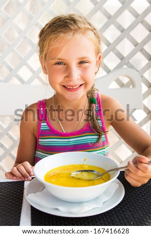 Cute child eating soup from the bowl, healthy food - stock photo