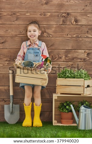Cute child girl caring for her plants. Cute little girl holding garden tools standing in the backyard. Spring concept, nature and care. - stock photo