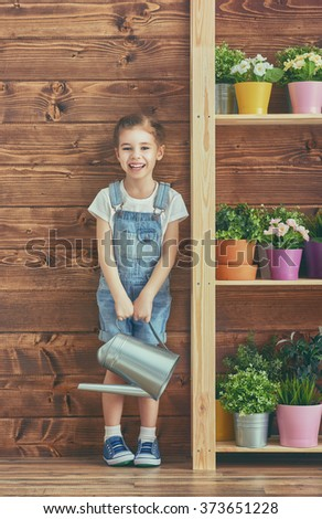 Cute child girl caring for her plants. Girl watering flowers in pots. Spring concept, nature and care. - stock photo