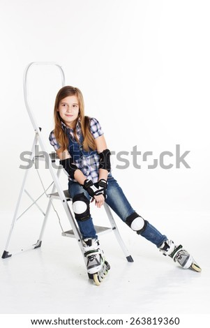 Cute child girl having fun in roller skates on a white background, studio shoot - stock photo