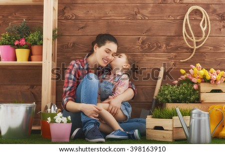 Cute child girl helps her mother to care for plants. Mother and her daughter engaged in gardening in the backyard. Spring concept, nature and care. - stock photo