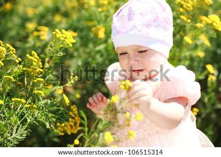 Cute child girl in yellow flower field