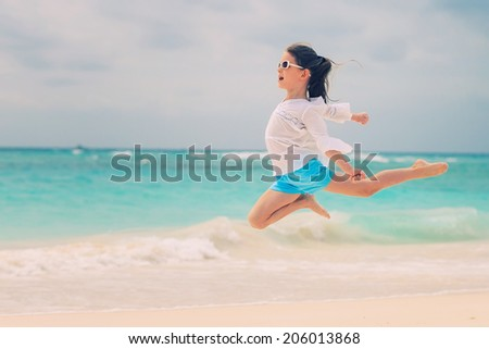 Cute child girl jumping on the beach.Photo processed instagram style - stock photo