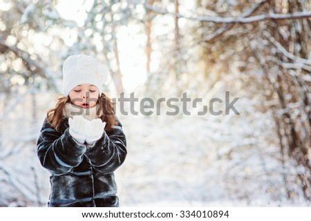 cute child girl playing with snow on the walk in winter forest. Outdoor activity on winter holidays. - stock photo