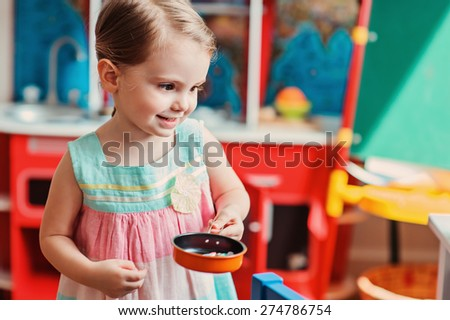 cute child girl playing with toy kitchen at home - stock photo