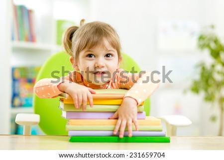 Cute child girl preschooler with books indoor - stock photo