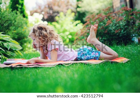 cute child girl reading book in summer garden outdoor. Kids learning on summer vacations. - stock photo