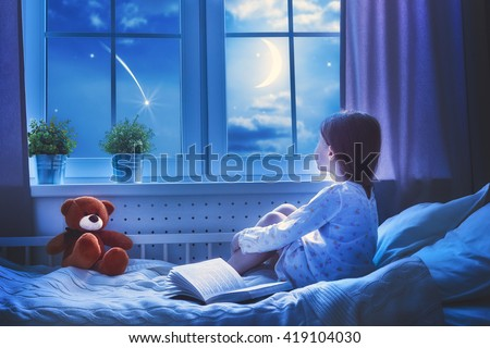 Cute child girl sitting at the window and looking at the stars. Girl making a wish by seeing a shooting star at bedtime night. - stock photo