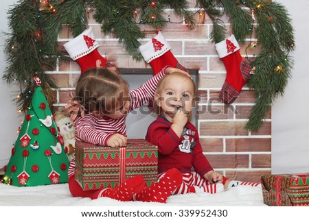 Cute child girl stroke smiling toddler sitting near Christmas decorated fireplace, winter holiday family concept