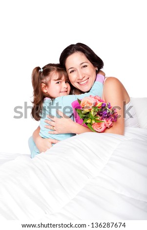 Cute child giving flowers and hug to mom in bed, mother day or hospital concept, isolated. - stock photo