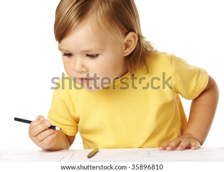 Cute child half-rise from table, playing with crayons, isolated over white