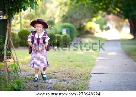 Cute child, happy little school girl, pupil of primary school in Australia, standing outdoors near pathway, ready to go to school for the first time
