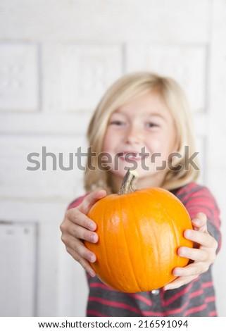 Cute child holding a small pumpkin - stock photo