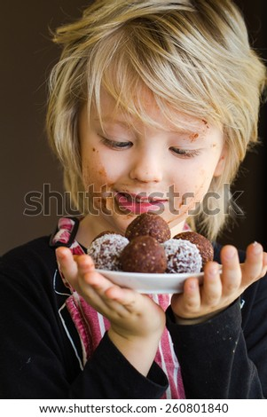 Cute child holding homemade chocolate balls as a treat - stock photo