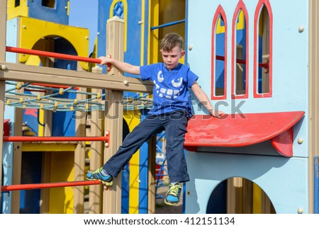 Cute child in blue climbing down ladder pole on colorful little house at playground - stock photo
