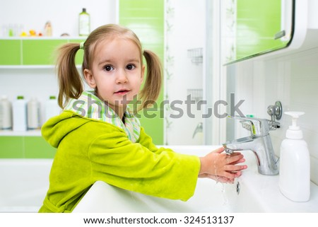 Cute child kid girl washing face and hands in bathroom