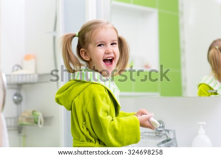 Cute child kid girl washing hands in bath room - stock photo