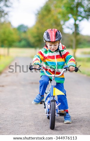 Cute child learning to ride a bike on summer day. Active leisure for children and little kids outdoors.