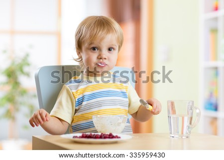 Cute child little boy eating food with spoon in nursery - stock photo