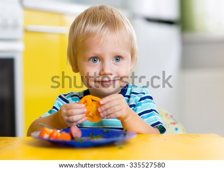 Cute child little boy eating his lunch sitting at a table in the kitchen - stock photo