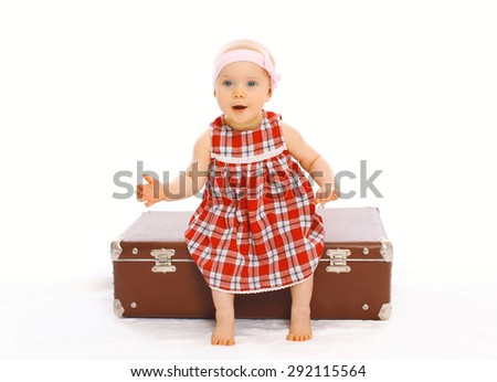 Cute child little girl in dress sitting on the suitcase playing and having fun - stock photo