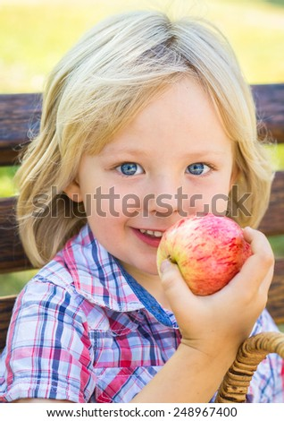 Cute child outdoors eating an apple as a healthy snack - stock photo