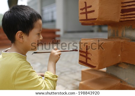 Cute child painting on building surface with happy