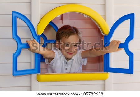 Cute child playing in toy house - stock photo
