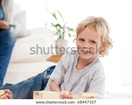 Cute child playing with dominoes in the living room with his parents - stock photo