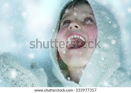 Cute child playing with snow.