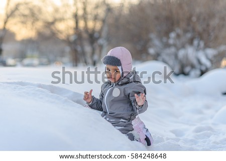 Cute child playing with snow in a winter park
